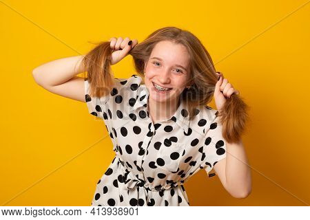 Funny Child With A Two-ponytail Hairstyle Smiles With Braces Grimaces And Laughs On A Yellow Backgro