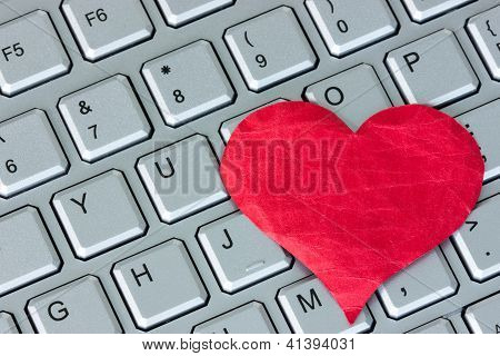 Red heart on the computer keyboard. Internet dating concept poster