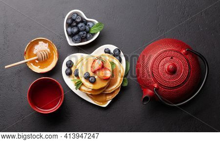 Healthy breakfast with pancakes and herbal tea. Homemade american pancakes with berries and honey. Top view flat lay