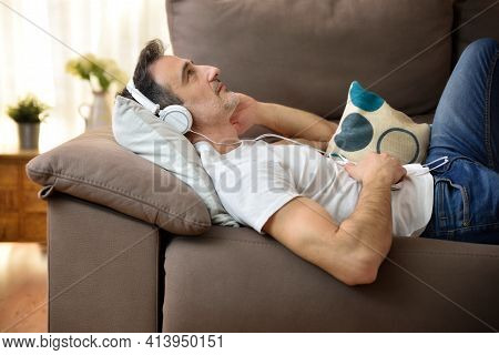 Relaxed Man Lying On A Sofa With Headphones On Listening To Music Staring Blankly