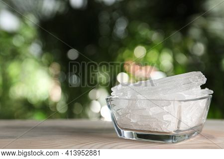 Menthol Crystals In Glass Bowl On Wooden Table Against Blurred Background. Space For Text