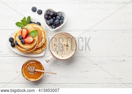 Breakfast with pancakes and espresso coffee. Homemade american pancakes with berries and honey. Top view flat lay with copy space