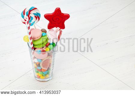 Various sweets assortment. Candy, bonbon, chocolate and macaroons in cocktail glass on wooden background. With copy space