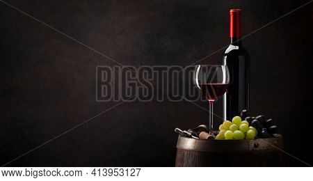 Wine bottle, glass of red wine, grapes on old wooden barrel. With copy space