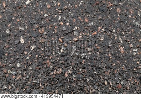Wet Road Surface. Tarmac Texture, Dark Road Pavement Consisting Of Crushed Rock Mixed With Tar. Back