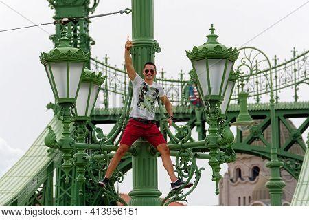 Budapest, Hungary, July 4: Joyful Young Man Gesturing Vigorously While Climbing The Lamppost Of The
