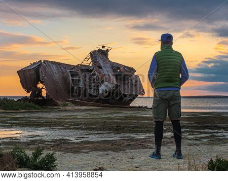 A Man Stands On The Shores Of The Aral Sea By An Old Abandoned Ship. Kazakhstan. The Ship Was Cut In