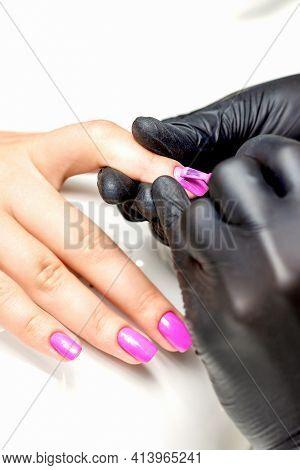Close Up Of Manicure Master Applying Pink Nail Polish To Female Nail In A Nail Salon