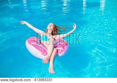 Woman Relaxing On Donut In The Pool Water In Hot Sunny Day. Summer Holiday Idyllic. Enjoying Suntan