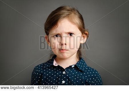 Perplexed Little Caucasian Kid Girl 4 -6 Years Old In A Blue Dress With Polka Dots On Grey Backgroun