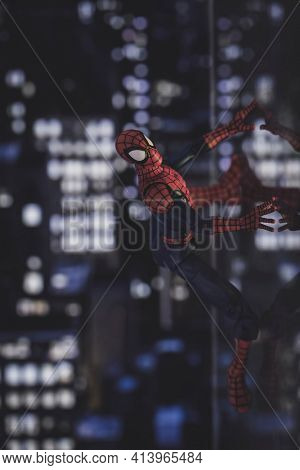 MARCH 23 2021: Marvel comics superhero Spiderman climbing the side of a building at night, reflections on glass window - Hasbro action figure