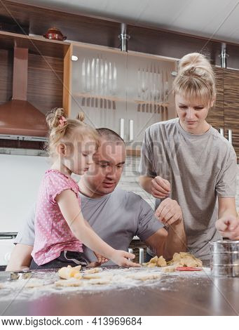 Happy Family, Father, Mother And Little Daughter Together Prepare Delicious Easter Cookies In The Ho