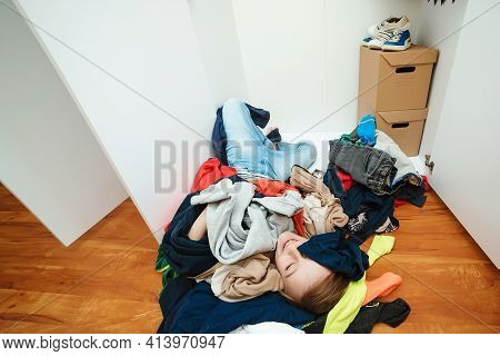 Lazy Boy Lying On The Thrown Clothes On The Floor. Mess In Open Wardrobe. Untidy Clutter Clothing Cl