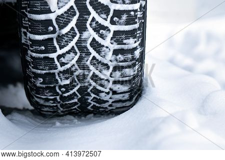 Winter Studded Tire Tread Standing In The Snow Close Up
