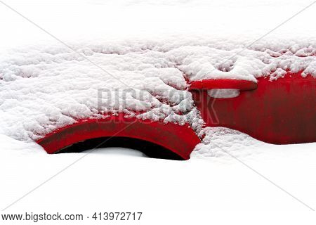 Fragment Of A Red Car Buried In Snow After A Snowstorm