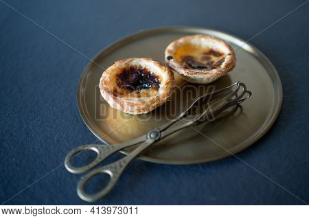 Two Delicious Belem Cakes (pasteis De Belem) On A Bronze Tray, With Serving Tongs.  Portuguese Sweet