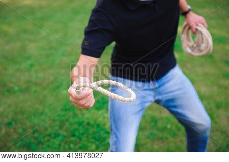Outdoor Games - Guy Playing Ring Toss In A Park.