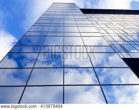 Grodno, Belarus - 03.22.2021: View Of A Modern Glass Skyscraper. Reflection Of A Cloudy Blue Sky In