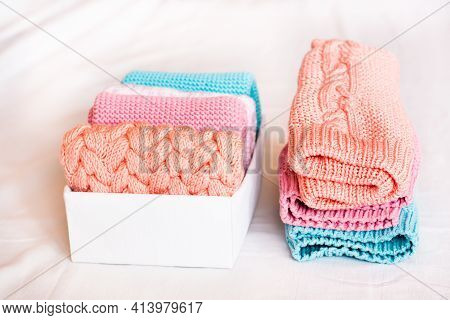 Organization And Order. A Stack Of Knitted Clothes Next To A Box Of Neatly Folded Items