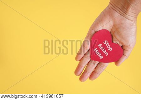 Stop Asian Hate , White Message, On Red Heart Paper In Hand With Yellow Background And Copy Space ,