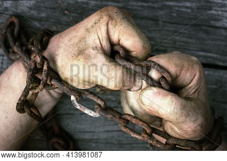 Male Hands Clenched Into Fists Chained With Old Rusty Chain On The Wooden Boards.