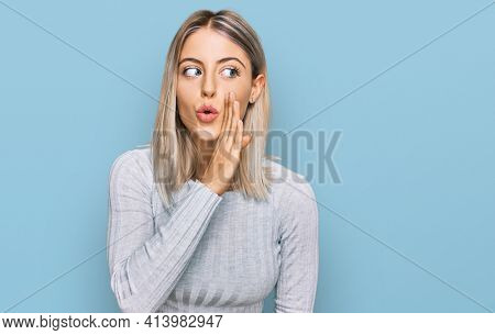 Beautiful blonde woman wearing casual clothes hand on mouth telling secret rumor, whispering malicious talk conversation
