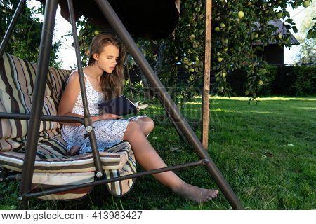 Teenage Girl Reads A Book Sitting On The Garden Swing In Summer Garden Under An Apple Tree