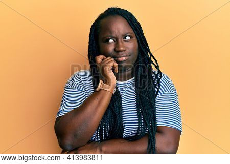Young black woman with braids wearing casual clothes thinking concentrated about doubt with finger on chin and looking up wondering