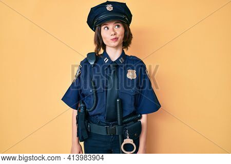 Young beautiful woman wearing police uniform smiling looking to the side and staring away thinking.