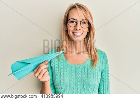 Beautiful blonde woman holding paper airplane looking positive and happy standing and smiling with a confident smile showing teeth
