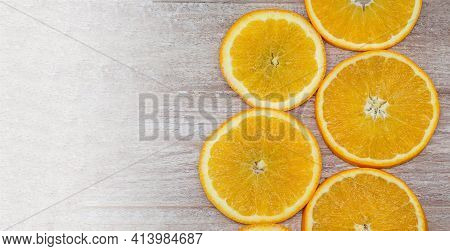 Oranges On A Wooden Background. Oranges Cut Into Circles.