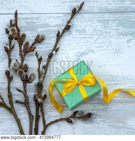 Gift Wrap And Willow Branches. Green Box With Yellow Ribbon. Green Gift Box On Wooden Background.