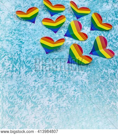 Lgbt-colored Paper Heart. A Heart Made Of Paper On A Blue Background. The Heart Is Rainbow Colored.