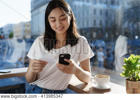 Young Asian Woman In T-shirt Sitting In Cafe Near Window, Sending Money Or Shopping Online With Plas
