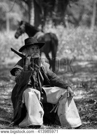 An Old Cowboy Sit And Rested His Horse After Working Hard In A Rural Farm Area