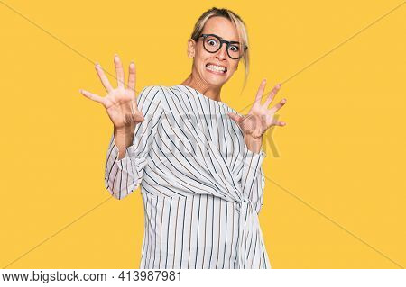 Beautiful blonde woman wearing business shirt and glasses afraid and terrified with fear expression stop gesture with hands, shouting in shock. panic concept.