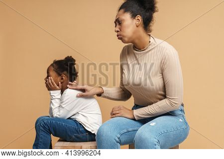 Displeased black mother touching her daughter after argument isolated over beige background