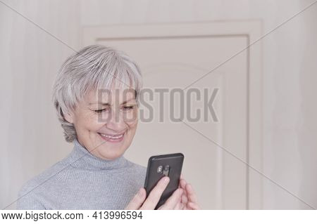 At Home Gray-haired Senior Woman In Gray Turtleneck Looks At Smartphone , Smiling.