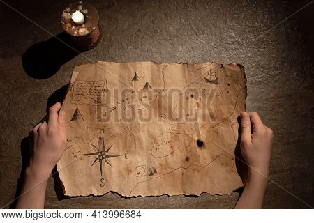 Old Treasure Map In Hands, Burning Candle, Concept Of Travel, Adventure, Search For Pirate Treasure