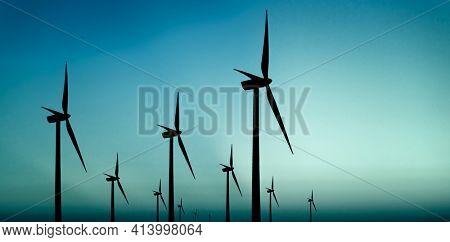 Wind turbines silhouette on blue background