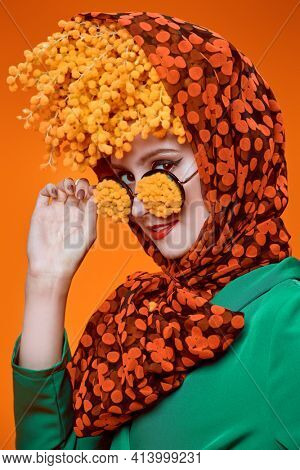Floral concept. Close-up art portrait of a high fashion woman posing with mimosa flowers on her head and glasses. Pin-up style.