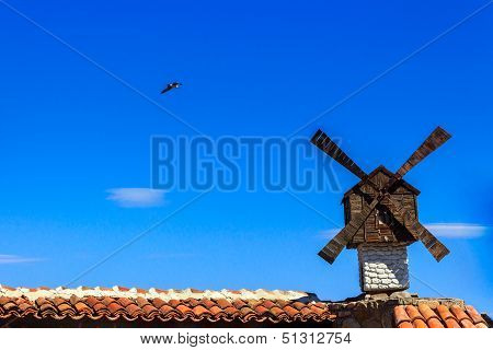 Windmill And Seagul On Background Of Blue Sky Over Building