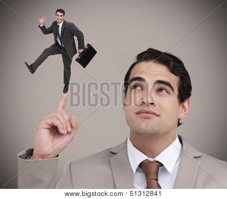 Businessman showing shrunk colleague with his briefcase dancing on his finger