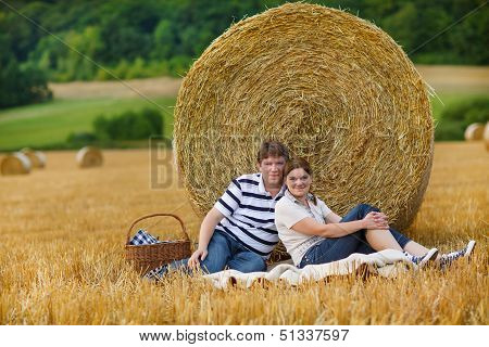Young Couple Picknicking On Yellow Hay Field On Summer Evening.
