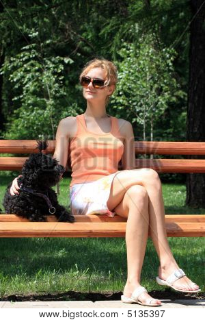 Beautiful woman enjoying the sun on a bench. poster