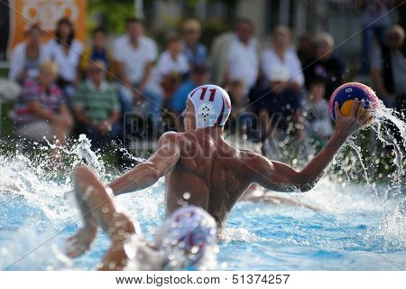 KAPOSVAR, HUNGARY - SEPTEMBER 15: Norbert Juhasz-Szelei (11) in action at a Hungarian championship water-polo game between Kaposvar (white) and Honved (blue) on September 15, 2013 in Kaposvar, Hungary