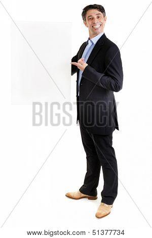 Suave businessman or salesman with an insincere cheesy toothy grin holding a blank sign and pointing to it with his finger, with copyspace for your text or advertisement