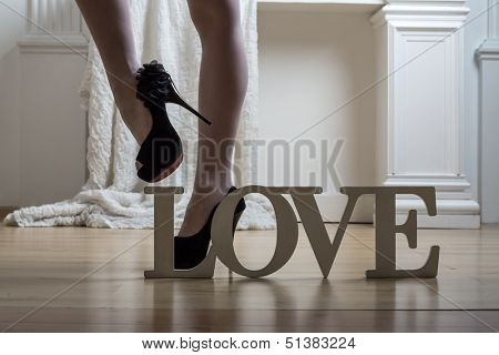 Beautiful female legs in stockings and black high-heeled shoes and the word Love on the floor