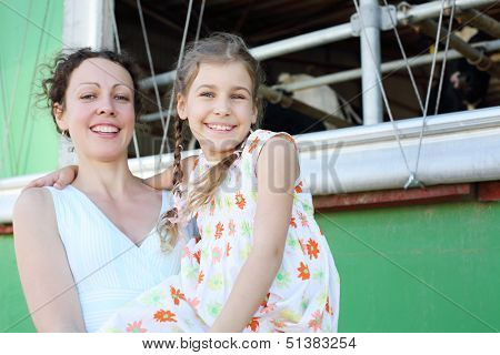 Beautiful mother and little daughter smile near stall with cows. Focus on girl.