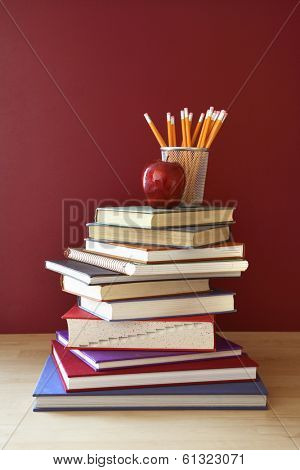 back to school still life with stack of books, apple, and pencils
